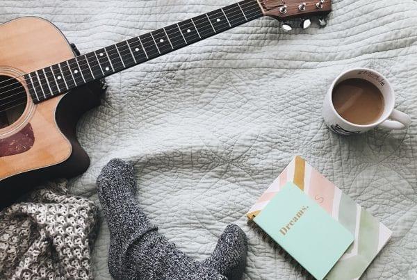 Gitarre liegt auf dem Boden neben Notizblock und Kaffee