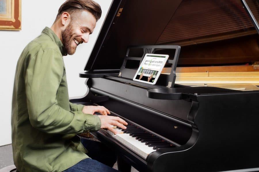 Mann spielt Klavier und verwendet Skoove auf dem Ipad