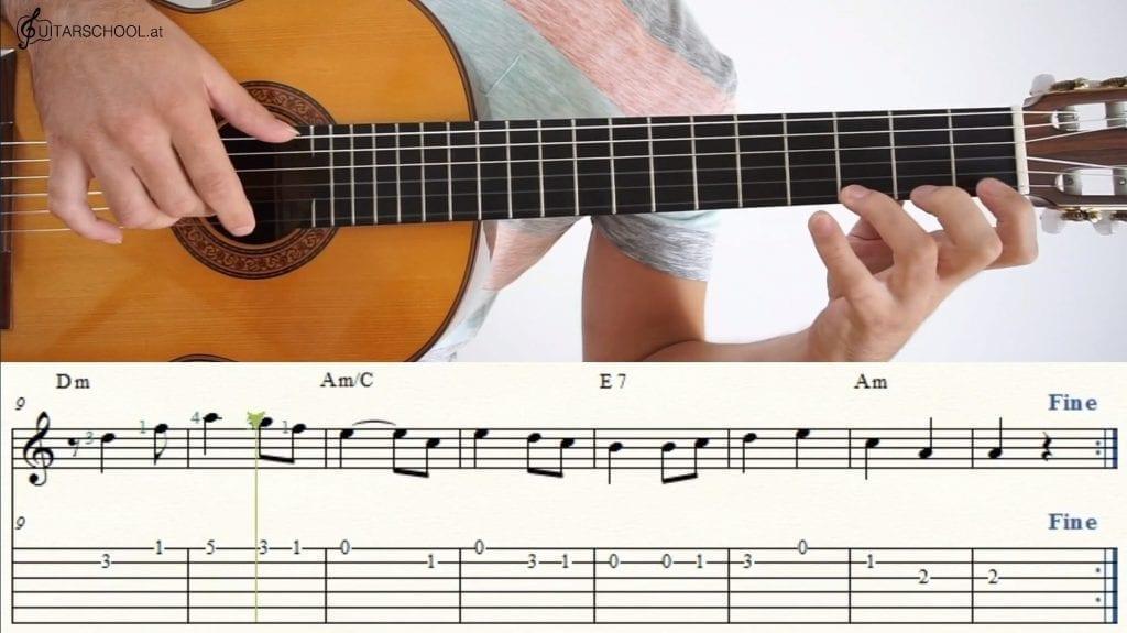 Auf dem Bild ist der Online Gitarrenkurs von Guitarschool zu sehen. Ein Mann spielt Gitarre und auf dem unteren Abschnitt ist der Notentext zu sehen.