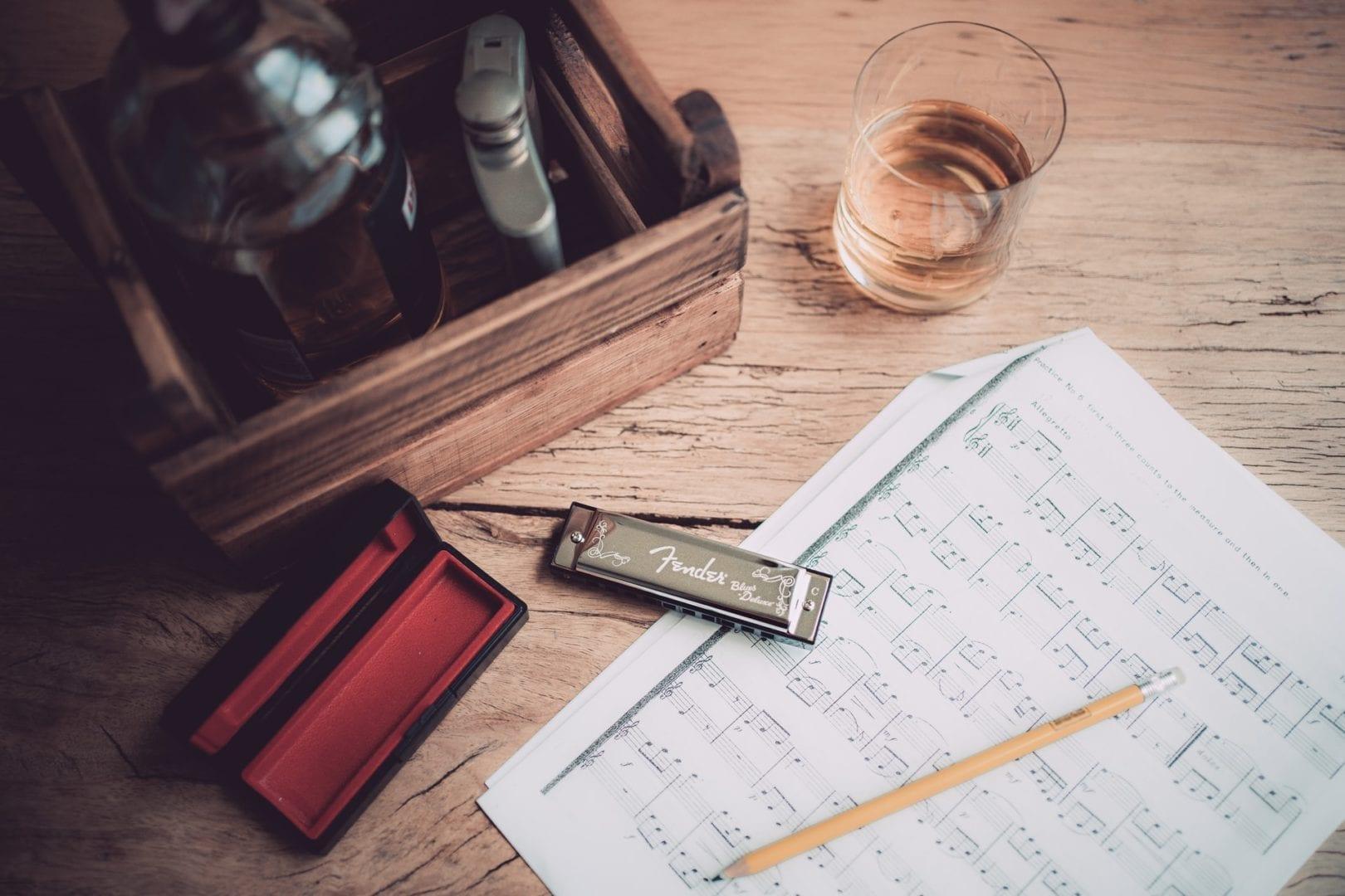 Mundharmonika liegt neben Tabulatur und Notentext
