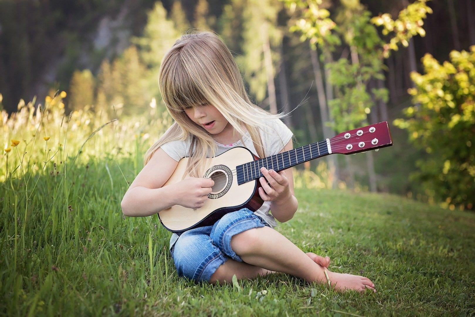 Kind sitzt auf der Wiese und lernt Gitarre
