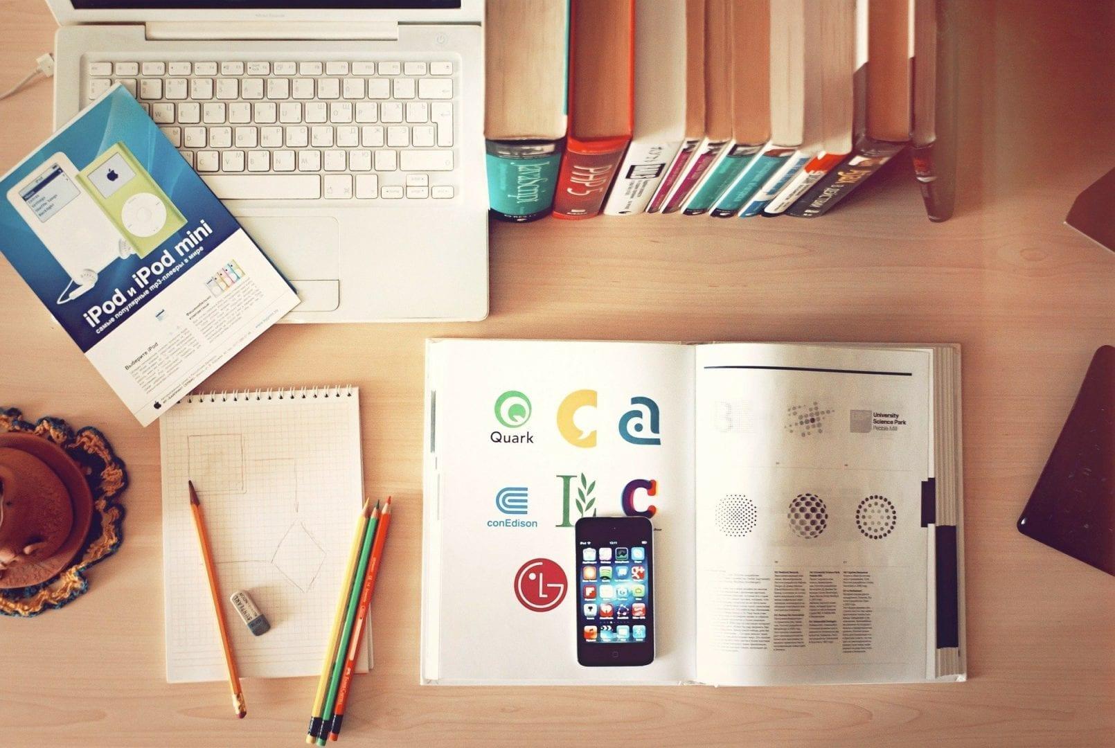 Ein Bild mit Laptop, Büchern und einem Lernheft